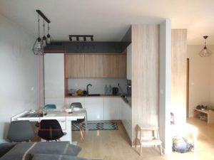 mała kuchnia z salonem ; drewniane frony ; białe fronty